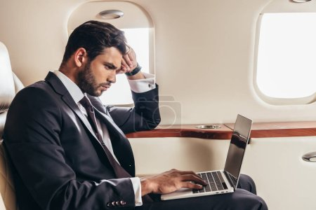Photo for Side view of handsome businessman in suit using laptop in private plane - Royalty Free Image
