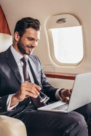 Photo pour Homme d'affaires souriant en costume à l'aide d'un ordinateur portable et portant des lunettes dans un avion privé - image libre de droit