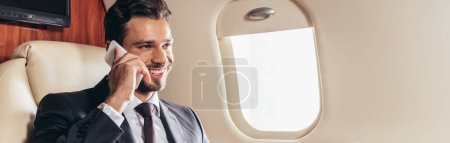 panoramic shot of handsome businessman in suit smiling and talking on smartphone in private plane