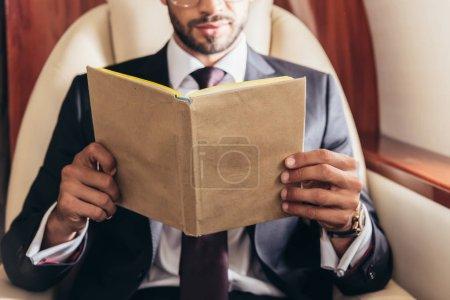 Photo pour Vue recadrée de l'homme d'affaires en costume livre de lecture en avion privé - image libre de droit
