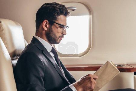 Photo pour Vue de côté du bel homme d'affaires en costume livre de lecture en avion privé - image libre de droit