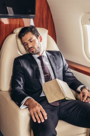 Photo pour Handsome businessman in suit with book sleeping in private plane - image libre de droit