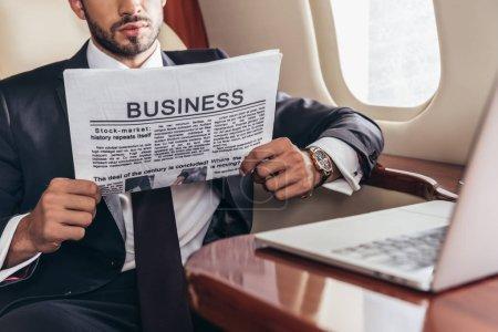 Photo pour Vue recadrée d'un homme d'affaires en costume lisant un journal d'affaires en avion privé - image libre de droit