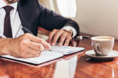 Photo pour Crochet vue d'un homme d'affaires écrivant dans un carnet en privé - image libre de droit