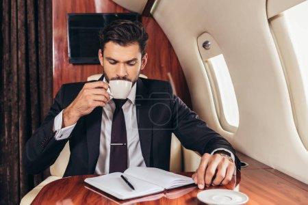 Photo pour Bel homme d'affaires en costume boire du café dans un avion privé - image libre de droit