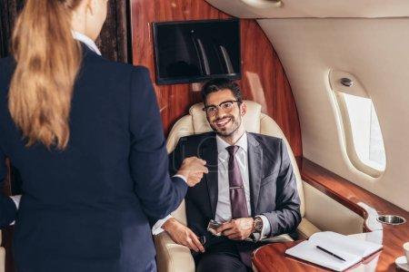 Photo pour Homme d'affaires souriant en costume regardant l'agent de bord dans un avion privé - image libre de droit