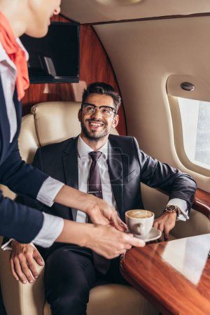 Photo pour Cropped view of flight attendant giving cup of coffee to handsome businessman in suit in private plane - image libre de droit