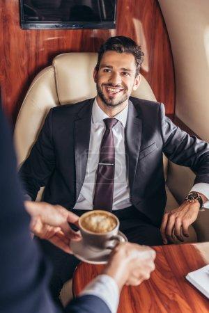 Photo pour Vue recadrée de l'agent de bord donnant une tasse de café à un bel homme d'affaires en costume dans un avion privé - image libre de droit