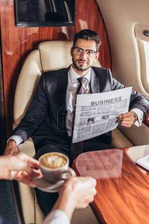 Photo for Cropped view of flight attendant giving cup of coffee to handsome businessman in suit in private plane - Royalty Free Image