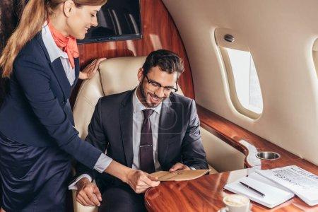 Photo pour Agent de bord donnant menu à un homme d'affaires souriant en costume dans un avion privé - image libre de droit