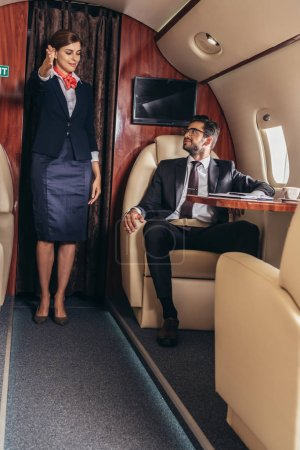 Photo for Flight attendant showing gesture to handsome businessman in suit in private plane - Royalty Free Image
