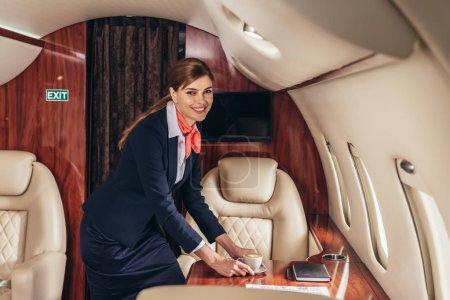 Foto de Asistente de vuelo sonriente poniendo taza de café en la mesa en avión privado - Imagen libre de derechos