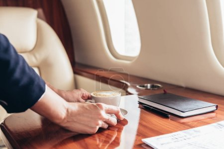 Photo for Cropped view of flight attendant putting cup of coffee on table in private plane - Royalty Free Image