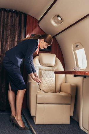 Photo pour Agent de bord en uniforme tenant sa ceinture de sécurité dans un avion privé - image libre de droit