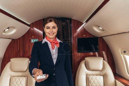 Foto de Auxiliar de vuelo sonriente en uniforme con mando a distancia en avión privado - Imagen libre de derechos