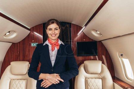 Photo pour Agent de bord souriant en uniforme regardant la caméra dans un avion privé - image libre de droit