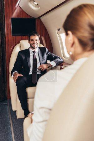 Photo pour Foyer sélectif de sourire homme d'affaires regardant femme d'affaires en avion privé - image libre de droit