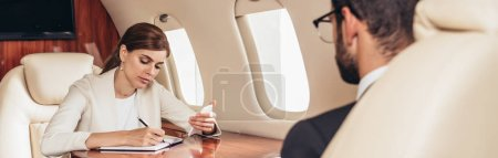 selective focus of businesswoman writing in notebook in private plane