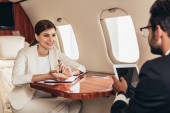 """Постер, картина, фотообои """"selective focus of businessman with digital tablet and businesswoman talking in private plane """""""