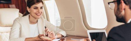 Photo pour Plan panoramique de l'homme d'affaires avec tablette numérique et femme d'affaires parlant en avion privé - image libre de droit