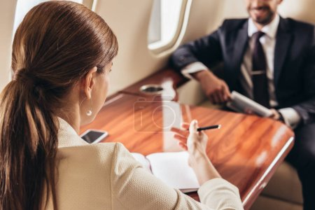 selective focus of businessman and businesswoman talking in private plane