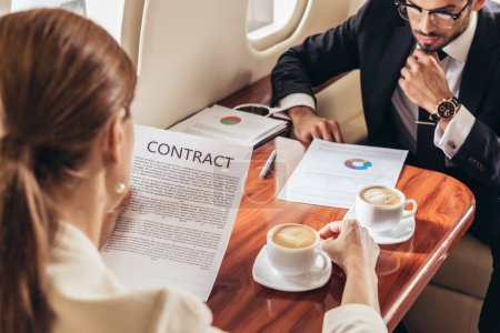 Photo pour Selective focus of businessman looking at document and businesswoman looking at contract in private plane - image libre de droit