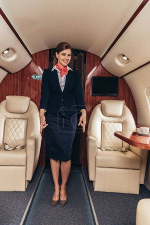 Photo for Smiling flight attendant in uniform showing gestures in private plane - Royalty Free Image