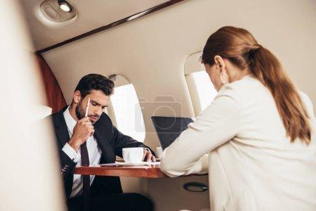 Photo pour Orientation sélective de l'homme d'affaires et de la femme d'affaires travaillant dans un avion privé - image libre de droit