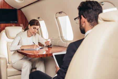Photo pour Homme d'affaires avec tablette numérique et femme d'affaires écrit dans un ordinateur portable en avion privé - image libre de droit