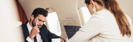 Photo for Panoramic shot of pensive businessman in suit in private plane - Royalty Free Image