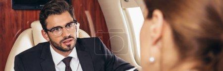 Photo pour Plan panoramique d'un homme d'affaires regardant une femme d'affaires en avion privé - image libre de droit