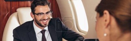 Photo for Selective focus of smiling businessman looking at businesswoman in private plane - Royalty Free Image