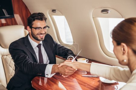 Photo pour Smiling businessman and businesswoman shaking hands in private plane - image libre de droit