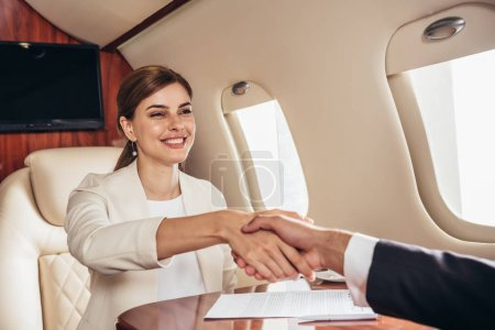 Photo for Smiling businessman and businesswoman shaking hands in private plane - Royalty Free Image