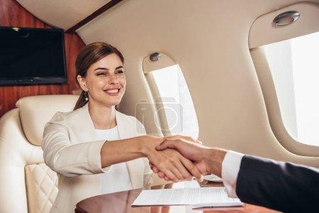 Photo pour Homme d'affaires souriant et femme d'affaires serrant la main dans un avion privé - image libre de droit