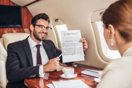 Photo pour Homme d'affaires souriant montrant contrat à une femme d'affaires en avion privé - image libre de droit