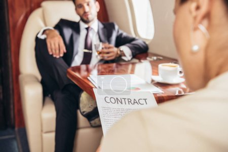 selective focus of businesswoman reading contract in private plane