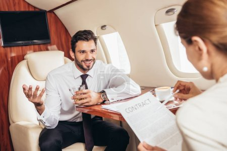 Photo for Selective focus of businessman looking at businesswoman with contract in private plane - Royalty Free Image