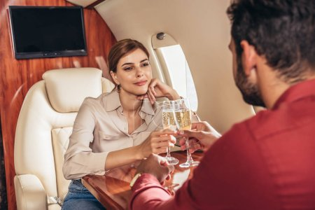 Photo for Boyfriend and girlfriend clinking with champagne glasses in private plane - Royalty Free Image