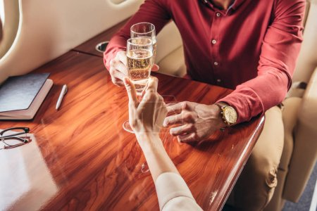 Photo for Cropped view of boyfriend and girlfriend clinking with champagne glasses in private plane - Royalty Free Image