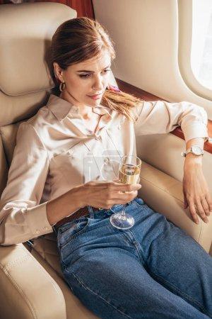 Photo pour Attractive woman in shirt holding champagne glass in private plane - image libre de droit