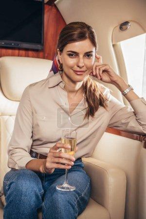 atractiva mujer en camisa sosteniendo copa de champán en avión privado
