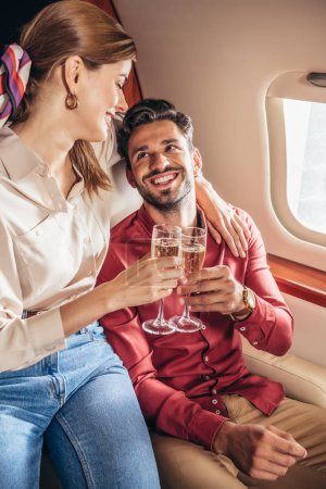 Photo for Smiling boyfriend and girlfriend clinking with champagne glasses in private plane - Royalty Free Image