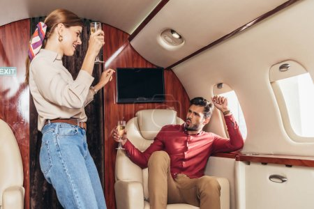 Photo for Smiling boyfriend and girlfriend holding champagne glasses in private plane - Royalty Free Image
