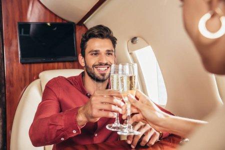 Photo pour Smiling boyfriend and girlfriend clinking with champagne glasses in private plane - image libre de droit
