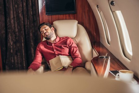 Photo for Handsome man in shirt sleeping with book in private plane - Royalty Free Image