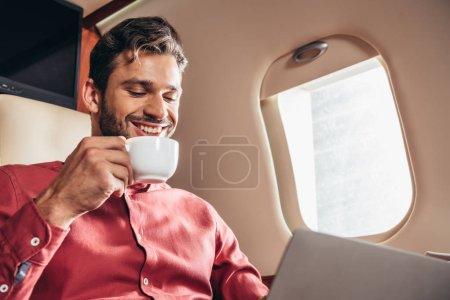 Photo pour Homme souriant en chemise à l'aide d'un ordinateur portable et tenant tasse dans un avion privé - image libre de droit