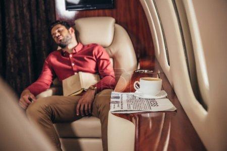Photo pour Bel homme en chemise dormant avec livre en avion privé - image libre de droit