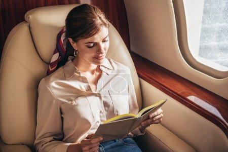 Photo pour Attrayant femme en chemise livre de lecture en avion privé - image libre de droit