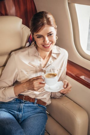 Photo for Smiling woman in shirt holding cup of coffee in private plane - Royalty Free Image